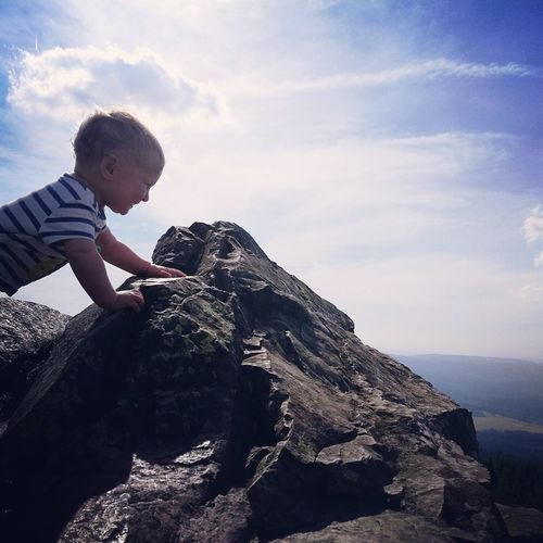 Side view of boy standing on rock against sky