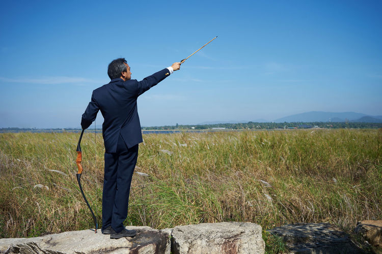 Businessman With Bow And Arrow On Field Against Sky
