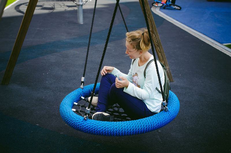 Full length of teenage girl sitting on swing at playground