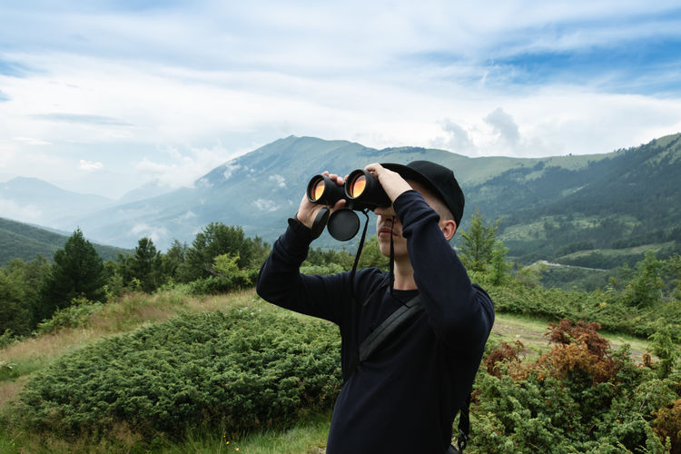 Teenage boy looking through binoculars while standing against mountains