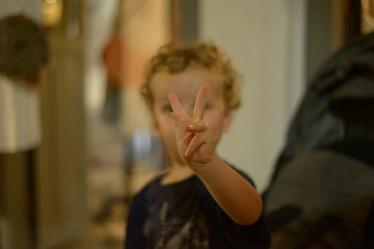 Boy gesturing over face at home