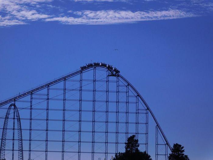 People Enjoying Rollercoaster Ride Against Sky