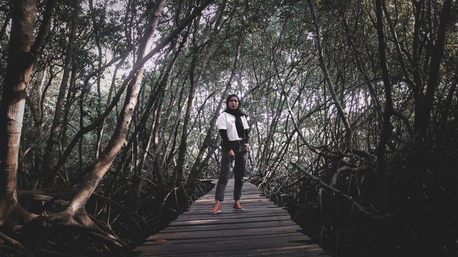 Full length of woman standing amidst plants in forest