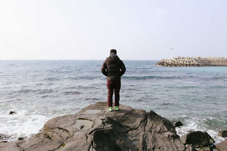 Jeju, South Korea Beach Casual Clothing Clear Sky Deep Jeju JEJU ISLAND  Jejudo Korea Leisure Activity Lifestyles Rear View Rock Rock - Object Sea Seoul Space Standing Thinking Tranquility Travel Traveling Volcano Wanderlust Water Waves