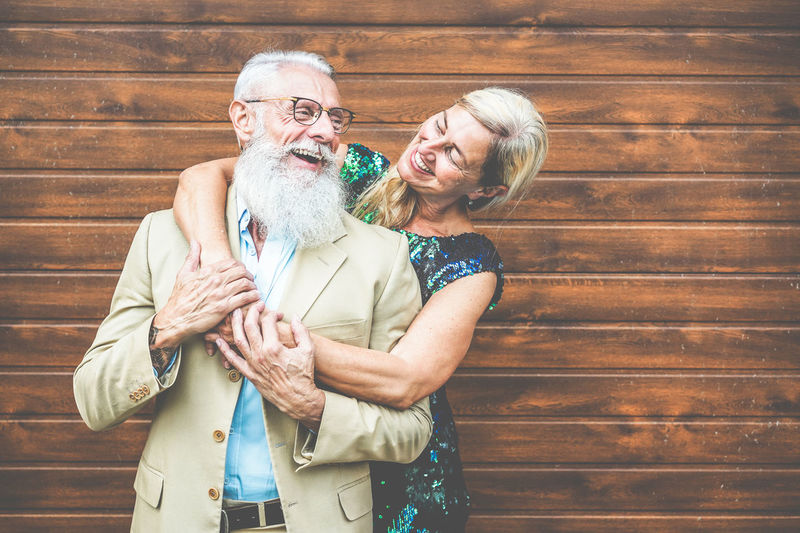 Smiling Woman Embracing Senior Man While Standing Against Wooden Door