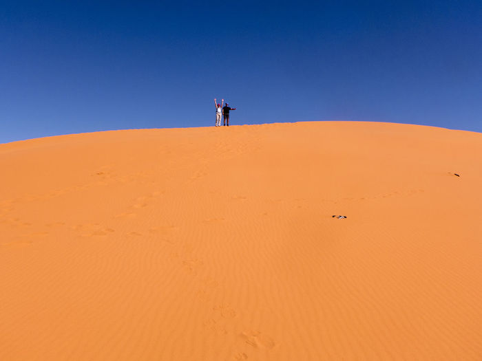 The Sahara Desert at its best. Fascinating desert landscape in the south of Morocco Erg Chebbi Morocco Sahara Land Sand Sand Dune Desert Climate Arid Climate Scenics - Nature Landscape Africa Pattern Merzouga People Two People Mountain Copy Space Tranquil Scene Orange Color Environment Nature Clear Sky Tranquility