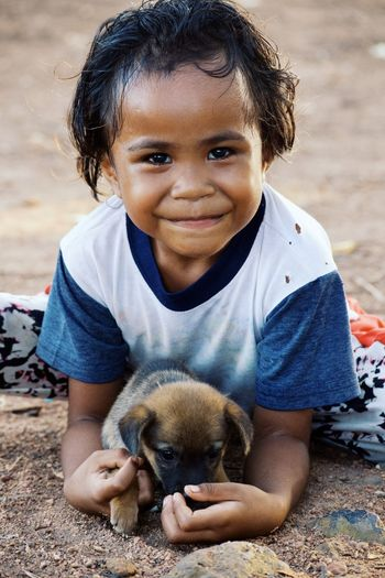 One Animal Animal Childhood Child Looking At Camera One Person Happiness Smiling Cute Portrait Outdoors Pets Young Animal Animal Themes Day Casual Clothing Holding Sitting Playing Dog Lifestyles Friendship Close-up Full Length Domestic Animals