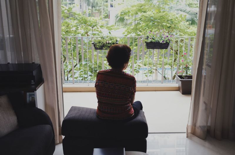 Rear view of woman sitting at home