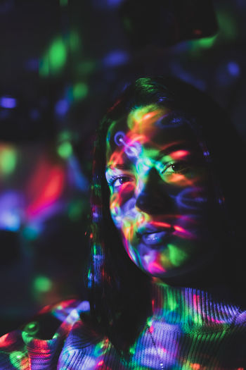 Close-Up Portrait Of Woman With Colorful Lights On Face In Nightclub