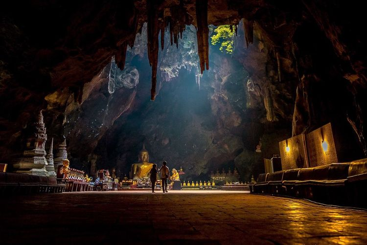 People Walking In Temple Under Cave