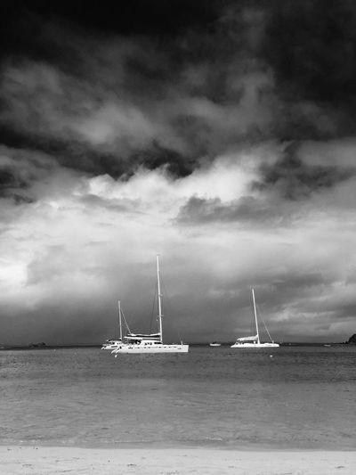 Sailboat sailing in sea against cloudy sky