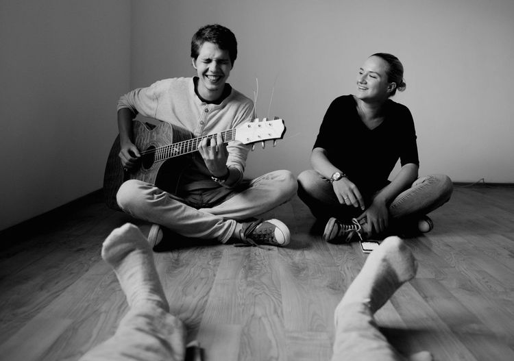 Young Man Playing Guitar By Friends On Hardwood Floor At Home