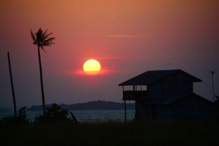 Silhouette house by sea against orange sky