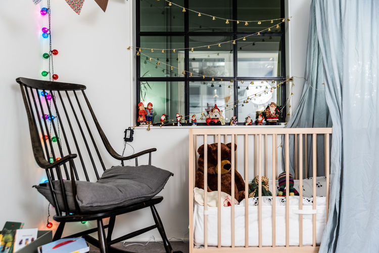 Empty chair by crib with decorations at home