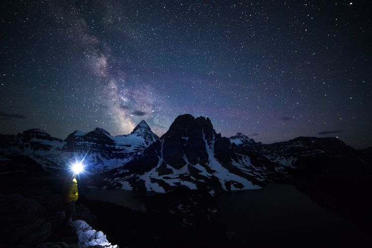 Hiker with illuminated headlight standing amidst mountains against sky at night