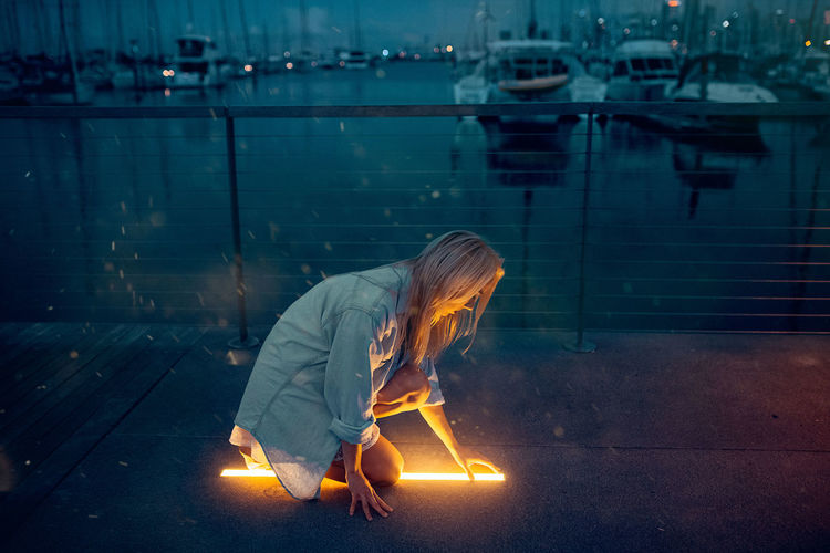 Woman with illuminated leaf in water