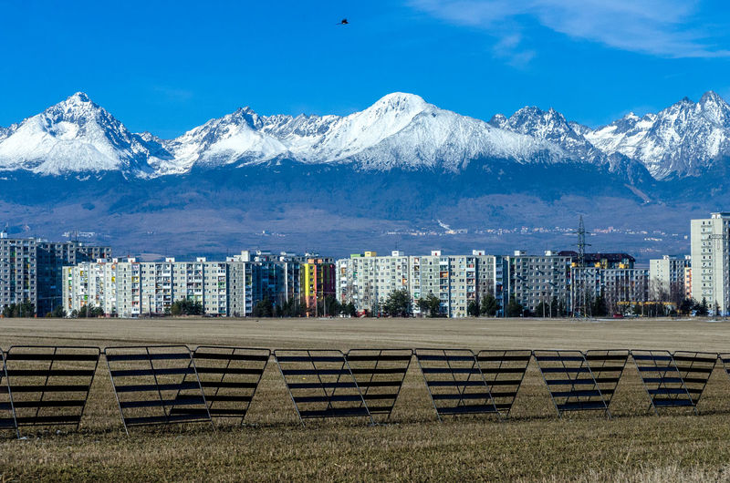 Scenic view of snowcapped mountains in front of buildings against blue sky