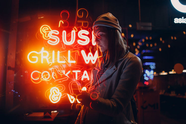 Woman standing by illuminated text at night