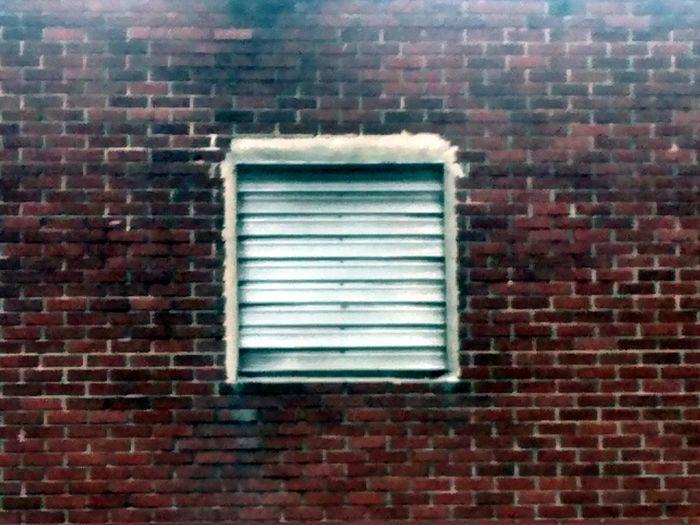 A Minimalist Photo of a ventillator near my Neighboorhood Drycleaners . Brick Wall Ventilator
