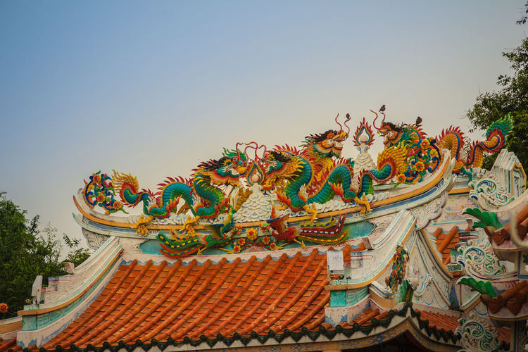 Beautiful large grimace dragons crawling on the decorative tile roof in Chinese temples. Colorful roof detail of traditional Chinese temple with dragon statue on blue sky background. Blue Sky White Clouds Chinese Temple Ancient Architecture Dragon Dragon Sculpture Blue Sky Blue Sky Background Chinese Culture Chinese Dragon Chinese Temple Chinese Temple Decoration Chinese Temples Crawling Decorative Decorative Art Decorative Object Dragon Scale Dragon Scales Dragon Shape Dragon Skin Dragon Statue Dragon Statues Dragon Stone Roof Detail Roof Details
