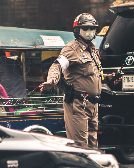 Traffic police Bangkok Police Thailand Traffic Gun Uniform Bangkok Street TukTuk Radio Masked Pollution Hand Raised Arm Raised Sunglasses Law Law And Order  Police Force Police Uniform Transportation One Person Real People Occupation Three Quarter Length Protection Helmet