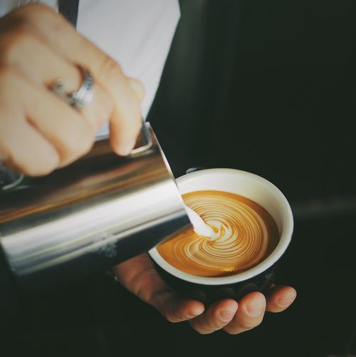 Close-up of hand pouring cream in coffee cup