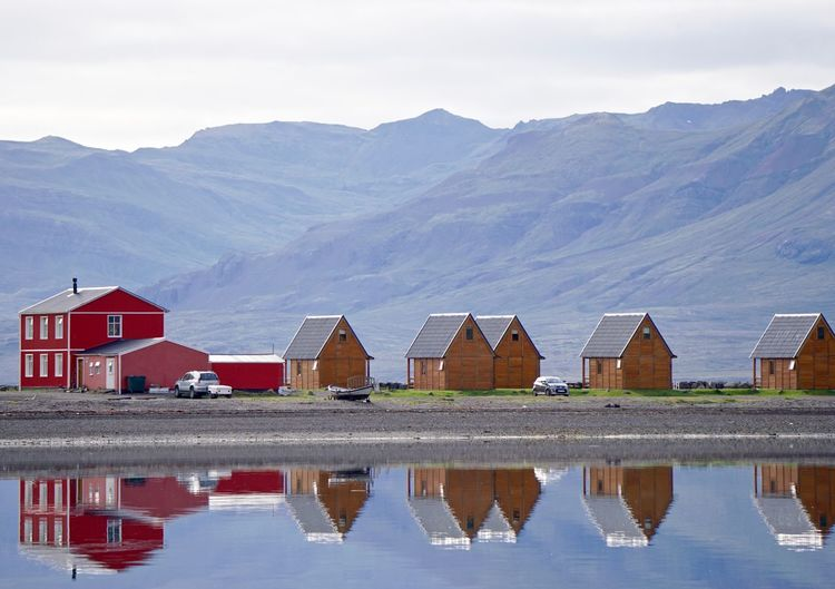 Reflection of houses in lake against sky