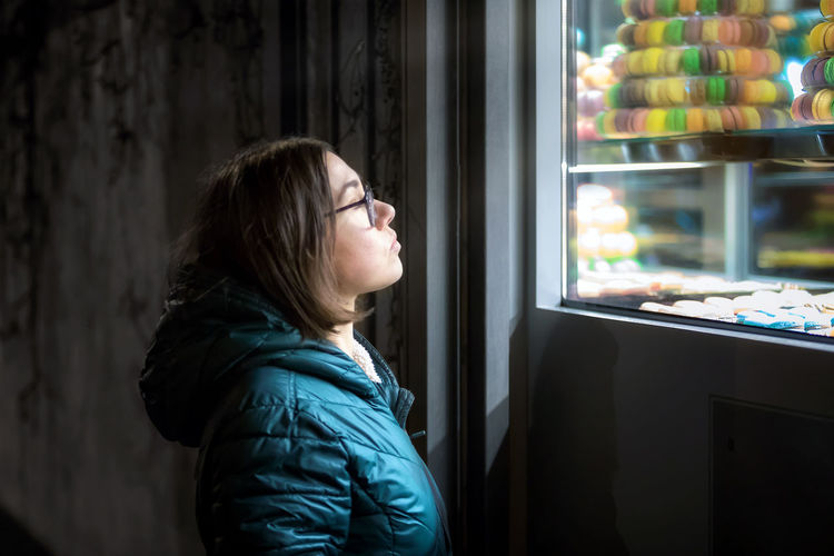 Side View Of Woman Looking At Macaroons On Window Display