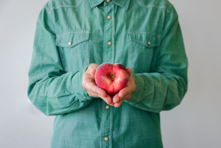 Midsection of man holding peach against white background