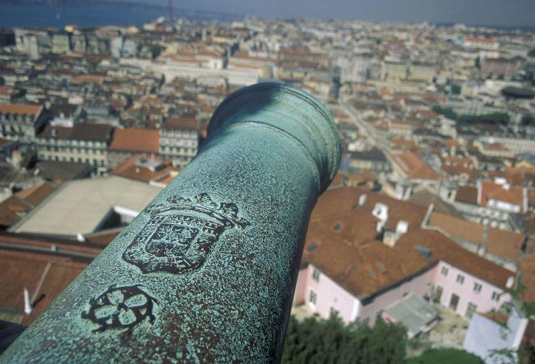 Cannon against cityscape