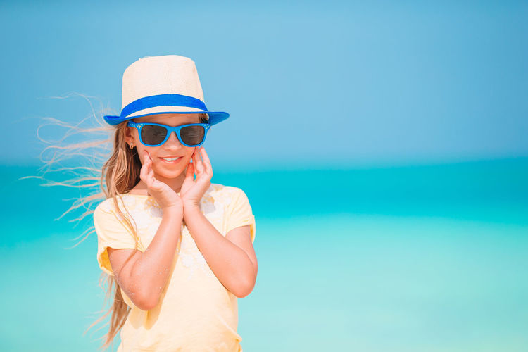 Woman wearing sunglasses against blue sky