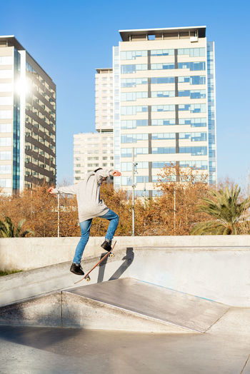 Man skateboarding on street against buildings in city