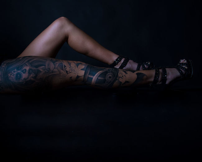 Low section of hipster woman with tattoo on leg against black background