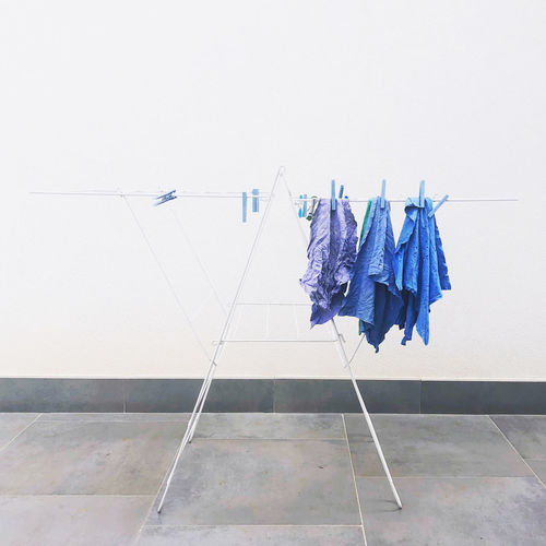 Low angle view of clothes hanging on clothesline against white wall