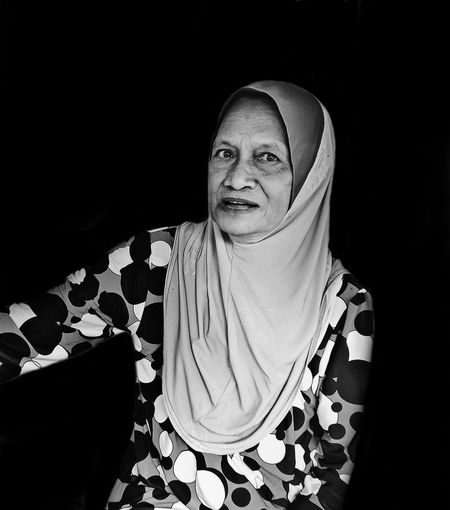 Portrait Of Woman In Hijab Sitting Against Black Background