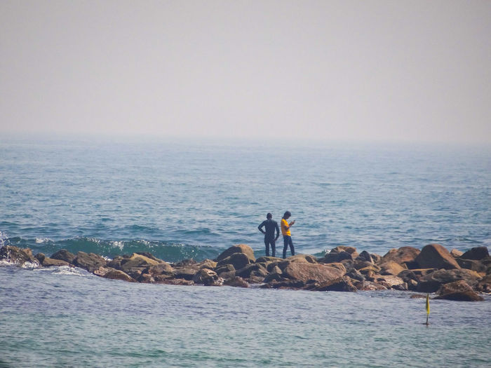 People standing on rocks at sea against clear sky