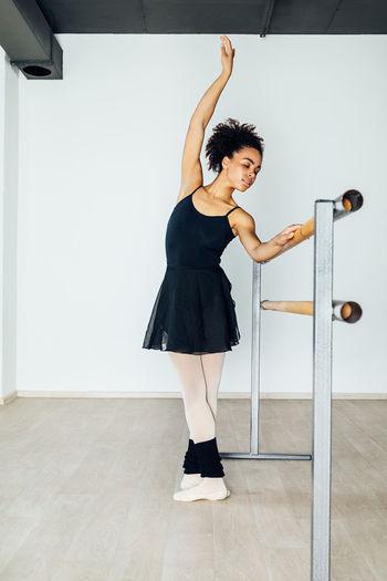 Full length of young woman dancing on floor in studio