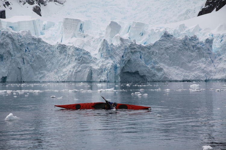 Person practicing rolling kayak in river against glacier