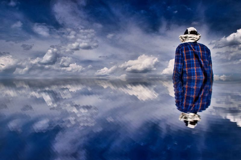 Rear view of man standing in lake against sky
