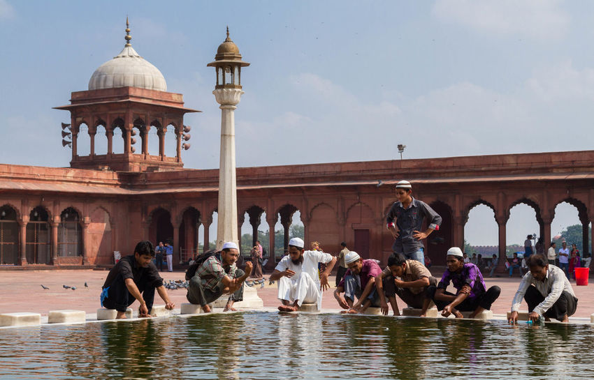 Man clean themselves in the courtyard of Jama Masjid. Commissioned by the Mughal Emperor Shah Jahan, it is the largest and best-known mosque in India. Architecture Bath Belief Clean Day Dome Incredible India Islam Mosque Muslim Newdelhi Outdoors People Prayer Religion Wash Water Young Adult