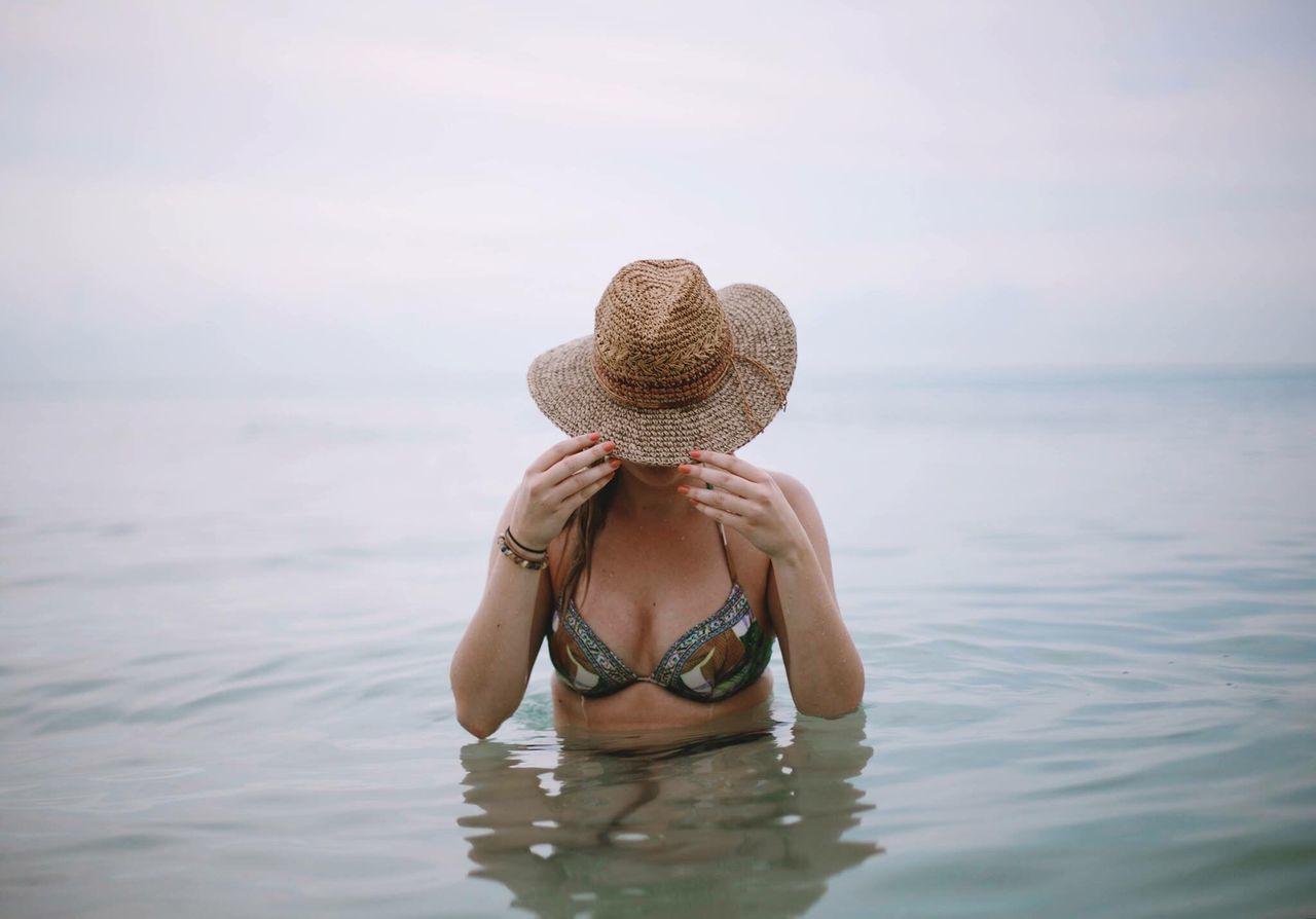 Sensuous Woman Wearing Bikini Holding Sun Hat While Standing In Lake
