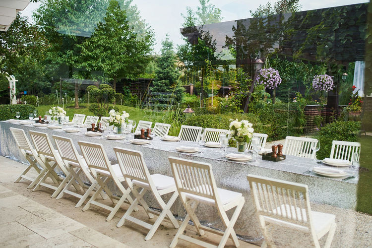 Empty chairs and tables at table in yard