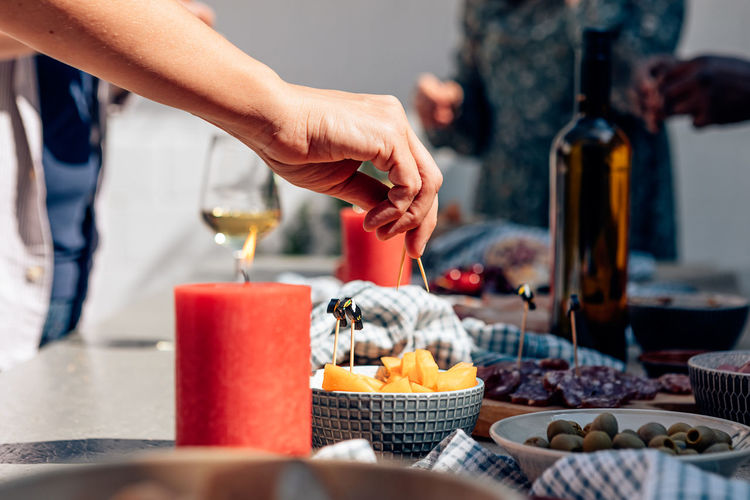 Female hand holding toothpick piercing a piece of melon on party table with aperitif snacks.