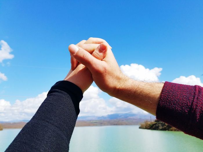 Cropped hands of couple over lake against sky