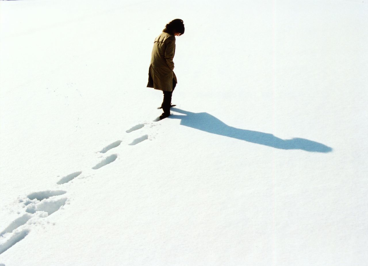 High angle view of woman walking in snow leaving behind footprints