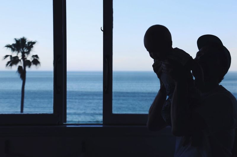Silhouette couple standing by sea against sky