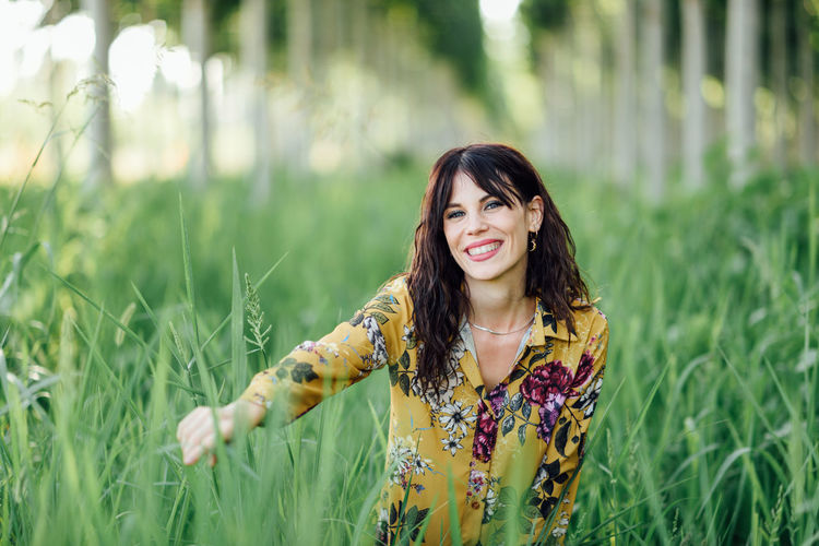 Portrait of smiling young woman standing amidst plants on field