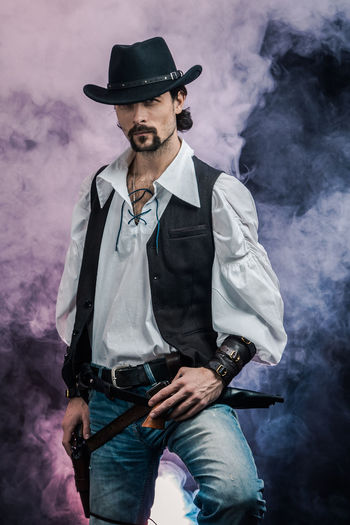 Handsome young man. This is an American cowboy. A vow to a white shirt, brown waistcoat and blue jeans. Black shoes on the feet. Carries a shtyapa, on a belt two pistols. The hair is of medium length; on the face is a beard and mustache. Authentic photo. Culture of America. Cowboy Wild West America American Gun National Authentic Moments Lifestyles Lifestyle One Person Candid Authentic Smoke - Physical Structure Hat Clothing Three Quarter Length Front View Real People Beard Holding Facial Hair Activity Young Men Casual Clothing Men