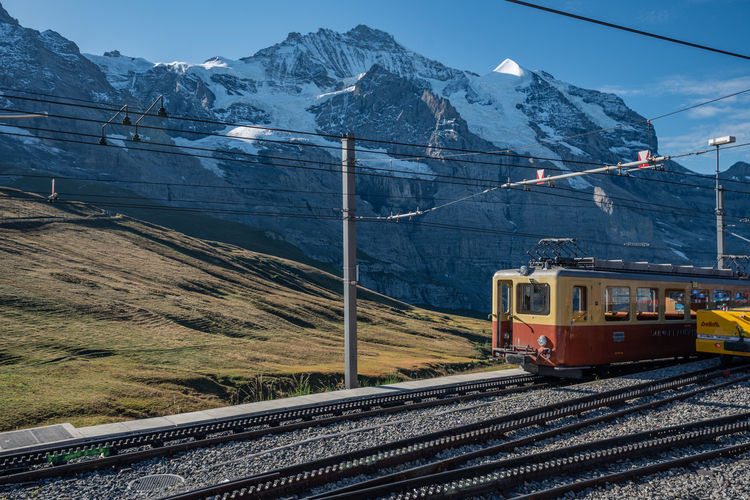Train on railroad track by snowcapped mountains against sky