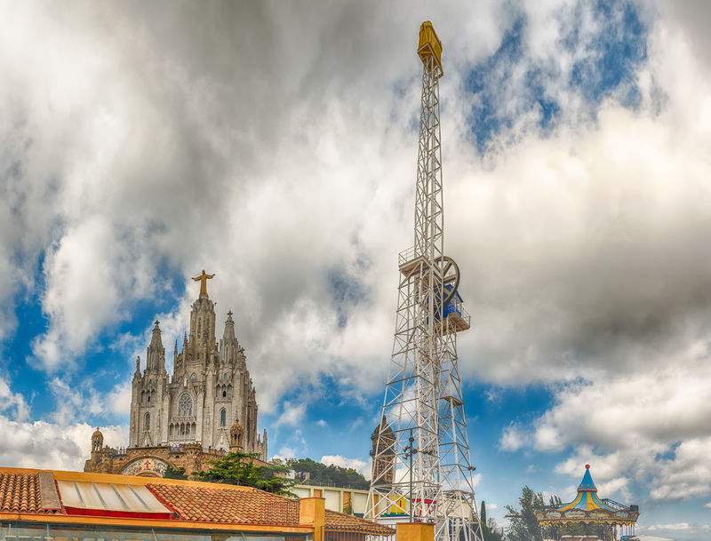 BARCELONA - AUGUST 12: Tibidabo Amusement Park and Church of the Sacred Heart, Barcelona, Catalonia, Spain on August 12, 2017. The park is among the oldest in the world still functioning Built Structure Architecture Building Exterior Cloud - Sky Sky Building Religion Spirituality Low Angle View Nature Place Of Worship Belief Day City Tower History The Past Travel Outdoors No People Spire